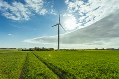 Wind turbines of a power plant for electricity generation in Normandy, France. Concept of renewable sources of energy. Country sunny landscape. Environmentally Stock Photos