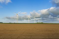 Wind turbines of a power plant for electricity generation in Normandy, France. Concept of renewable sources of energy. Agricultural fields. Environmentally Stock Photo