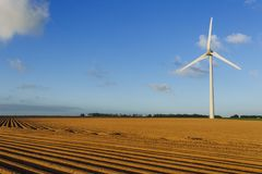 Wind turbines of a power plant for electricity generation in Normandy, France. Concept of renewable sources of energy. Agricultural fields. Environmentally Royalty Free Stock Image