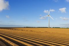 Wind turbines of a power plant for electricity generation in Normandy, France. Concept of renewable sources of energy. Agricultural fields. Environmentally Stock Image