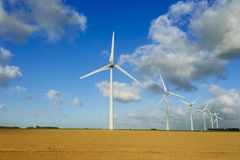 Wind turbines of a power plant for electricity generation in Normandy, France. Concept of renewable sources of energy. Agricultural fields. Environmentally Royalty Free Stock Photography