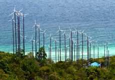The wind turbines produce electricity. The wind turbines produce electricity behind the sea Stock Images
