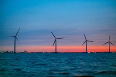 Wind turbines producing energy along the coastline. Marine lands royalty free stock images