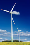 Wind turbines in rape field. Wind turbines in golden rape field against a deep blue sky Stock Photos