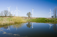 Wind turbines reflection. Several wind turbines in green fireld, reflected in a small pond Stock Photos