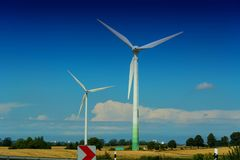 Wind turbines for renewable energies. Windmill turbines with partially cloudy blue sky in the background. Wind turbines for renewable energies royalty free stock photos