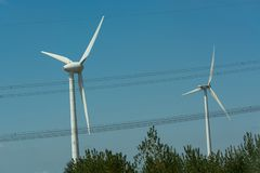 Wind turbines for renewable energies. Windmill turbines with partially cloudy blue sky in the background. Wind turbines for renewable energies royalty free stock image