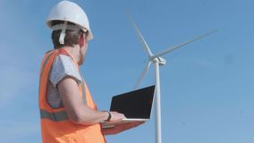 Wind turbines are revolving while a technician is operating a laptop. Clean, eco-friendly energy concept. A male