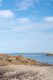 Wind turbines in rocky coastal ocean landscape Stock Photos