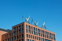 Wind turbines on the roof of building Stock Photos