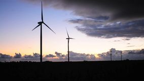 Wind turbines in a row at sunset stock video footage