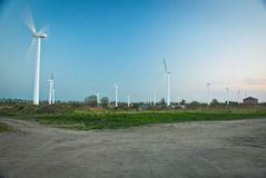 Wind turbines. Several wind turbines in a green field, against a blue sky Royalty Free Stock Photography