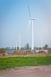 Wind turbines. Several wind turbines in a green field, against a blue sky Stock Photo