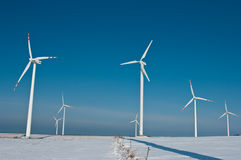 Wind turbines and shadow. Several wind turbines in a white field, against a blue sky. The shadow of a wind turbine seen in the foreground Royalty Free Stock Photography