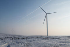 Wind turbines silhouette. Wind turbines on field with snow and fog Stock Photos