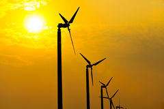 The wind turbines silhouette generating electricity in the sunse. T sky royalty free stock image