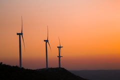 Wind turbines silhouette on the mountain during sunset. Couples of Wind turbines silhouette on the mountain during sunset Royalty Free Stock Image