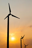 Wind turbines silhouette on sunset background. Stock Photos