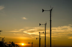 Wind turbines silhouette in the sunset sky Stock Images