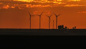 Wind turbines silhouettes on sunset. Wind turbines silhouettes on orange sky background Stock Photos