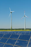 Wind turbines and solar panels against a rapeseed Royalty Free Stock Photos