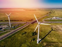 Wind turbines and solar panels in huge green field surrounded by highway stock image