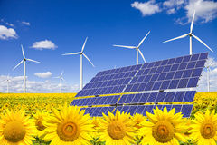 Wind turbines and solar panels on sunflowers field. Against a blue sky. Clean energy concept Stock Image