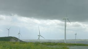 Wind turbines spinning in green field under gray stormy sky, bad rainy weather. Stock footage stock video
