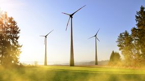 Wind turbines in spring landscape at sunrise. Royalty Free Stock Photo