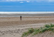 Wind Turbines on the horizon at Crosby Beach,England. Wind Turbines stand in rows on the horizon at an empty Crosby beach,Merseyside,England Stock Images