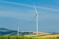 Wind turbines standing on a heels among fields Royalty Free Stock Images