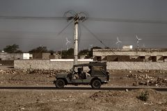 Wind turbines, stone houses, power lines, people in an army jeep royalty free stock photos
