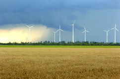 Wind turbines in storm. Wind turbine park during a big thunderstorm with rain and snow royalty free stock photos