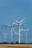 Wind turbines in strong heat haze (!). Wind turbines and in the foreground a power transmission line, there is very strong heat haze over the field in the Stock Image
