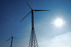 Wind turbines and sun. Two wind turbines silhouettes and sun shining royalty free stock photography