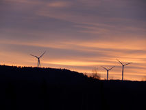 Wind Turbines at Sunrise in Vermont. Beautiful sunrise over Vermont mountains with wind turbines in silhouette. Gorgeous colors, orange, pink, yellow, purple Stock Photo