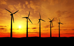 Wind Turbines at sunset. Row of wind turbines silhouetted in countryside with colorful sunset and cloudscape in background Royalty Free Stock Image