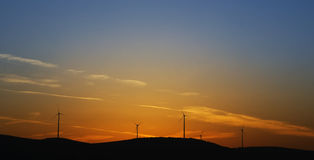 Wind turbines on sunset. Orange sunset with wind turbines silhouettes Stock Photography