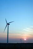 Wind turbines at sunset. Scenic view of two wind turbines in countryside with sunset and blue sky background Royalty Free Stock Images