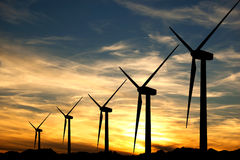 Wind turbines in a sunset. Some wind turbines silhouette in the sunset sky Royalty Free Stock Photos