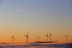 Wind turbines at sunset. An array of wind turbines at sunset with low clouds covering the bases and a jet airplane flying overhead Stock Images