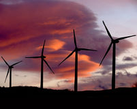 Wind turbines at sunset two. Wind turbines back lighted by setting sun and clouds royalty free stock photography