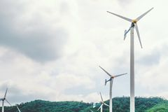 Wind turbines to produce electricity for renewable energy on mountain and cloudy sky. Background Stock Photography