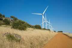 Wind turbines and track in the countryside Stock Photos