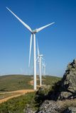 Wind turbines, track and rocks in the countryside Stock Photos