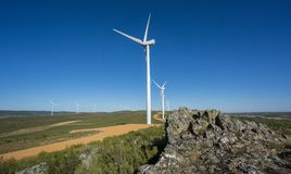 Wind turbines, track and rocks in the countryside Stock Images