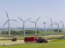 Wind turbines and tractors. Windmills in windfarm with tractors working in foreground royalty free stock photography