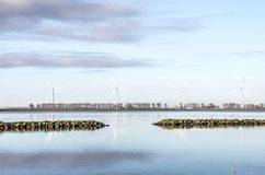 Wind turbines on a tranquil morning. View across the calm waters of Haringvliet estuary towards the wind turbines on the other side Stock Photos