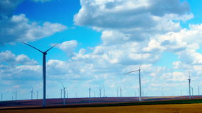 Wind Turbines With Turquoise Sky, Green Energy. Time Lapse, Tilt. Concept Of Using Natural Resources Intelligently. Wind energy turbines are one of the stock footage