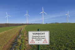 Wind turbines and warning sign. Four wind turbines and a warning sign Stock Photo